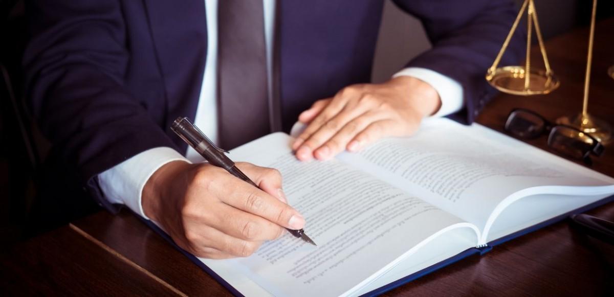 prawnik piszący po dokumentach