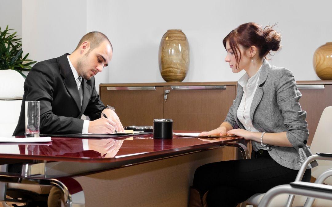 Dwie osoby, biuro. Udzielanie kredytu. Mężczyzna podpisuje dokument. dziedziczenie udziałów, kredyty frankowe warszawa, kredyty frankowe bydgoszcz, frankowicze