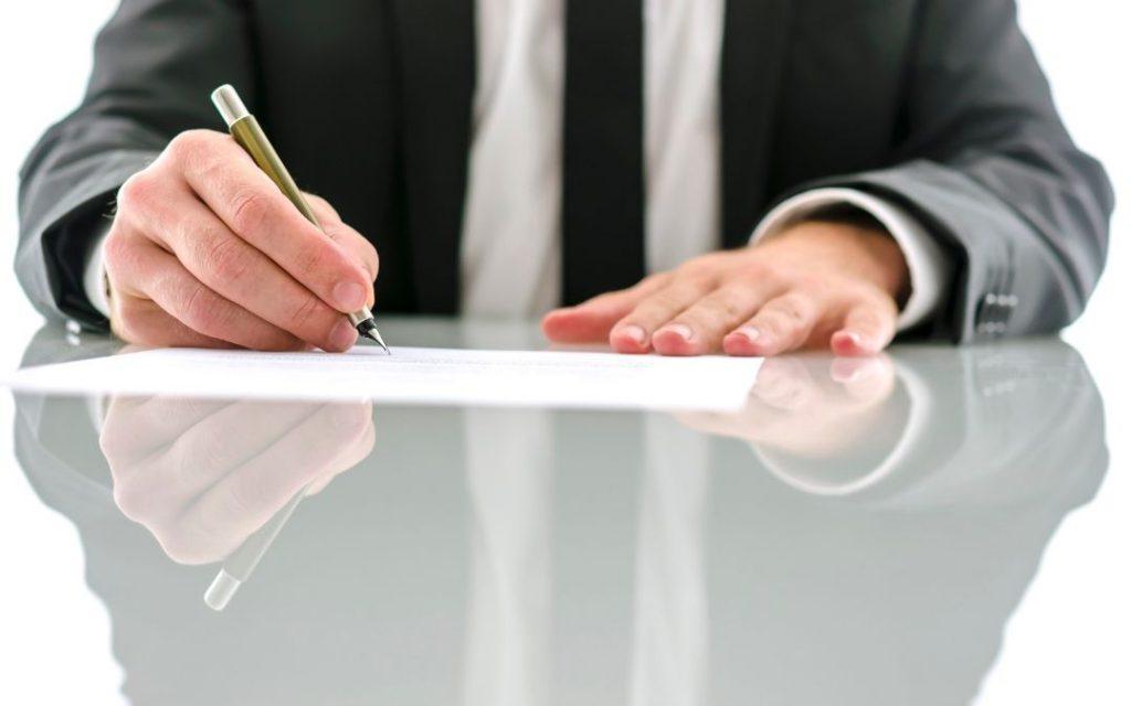 meżczyzna podpisuje dokument kredyty frankowe bydgoszcz