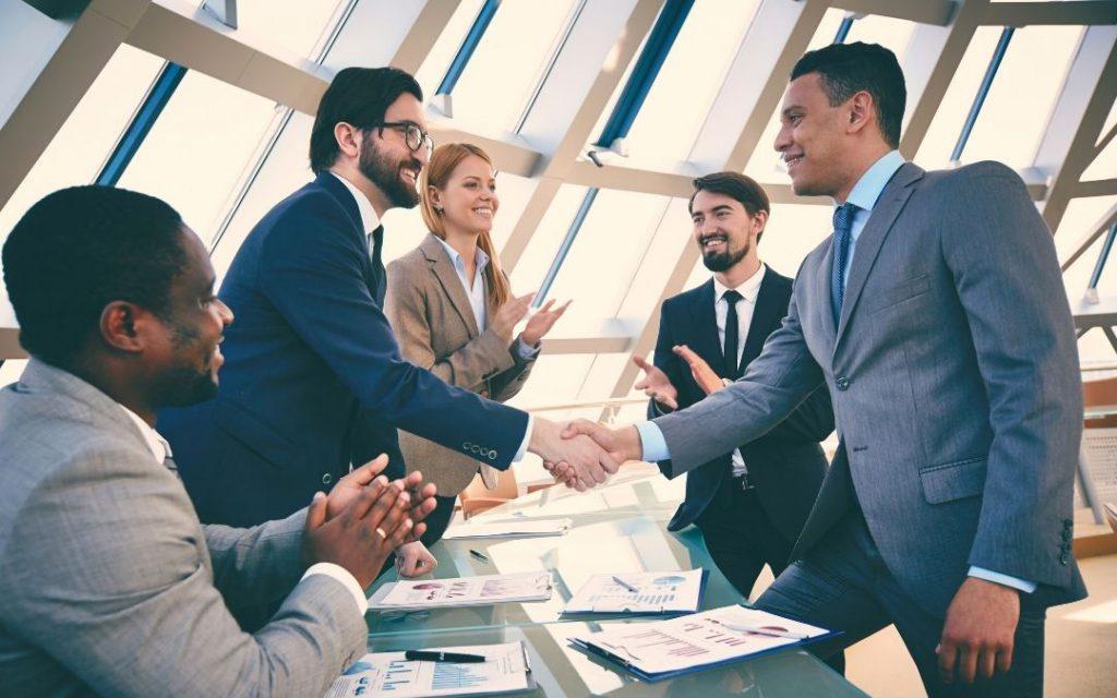 grupa osób na spotkaniu, podają sobie dłonie, zarządzanie kredytem frenkowym